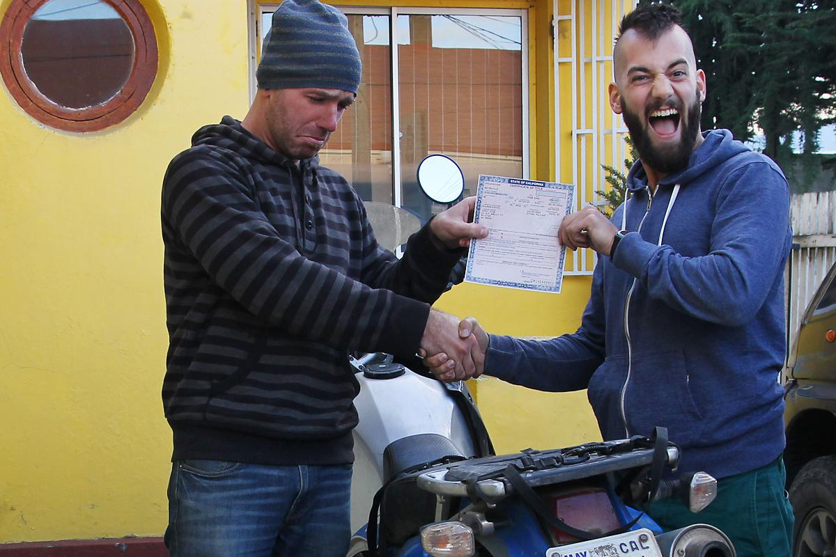 21,219 - Punta Arenas -- Sean hands over the motorcycle title to Leo, its new owner, to start a trip back north.